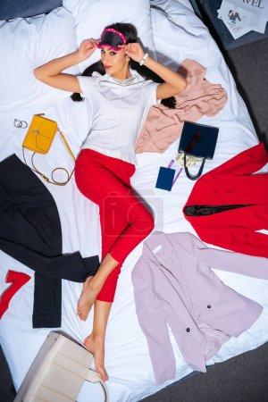 Foto de Vista superior de una mujer joven en la máscara de ojo mirando a cámara mientras se está acostado en la cama con ropa elegante, pasaporte, tarjeta de embarque y billetes de dólar - Imagen libre de derechos