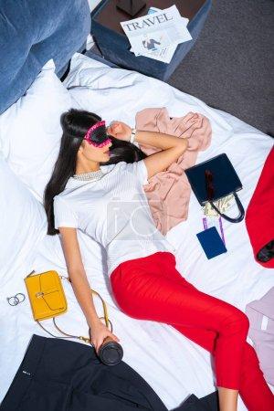 Photo pour Vue de la forte inclinaison de la jeune femme au masque d'oeil dormant sur le lit avec le café pour aller, passeport et carte d'embarquement - image libre de droit