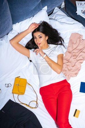 Photo pour Vue d'angle élevé de jeune femme avec le doigt sur les lèvres en regardant la caméra en position couchée sur le lit - image libre de droit