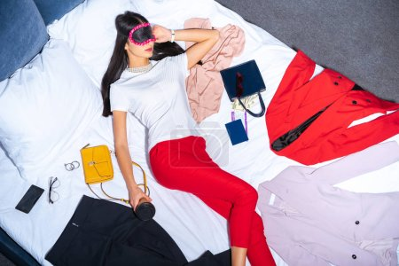 top view of girl in eye mask holding coffee to go and sleeping on bed with clothes, passport and money