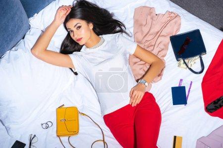 Photo pour Vue de dessus de belle fille regardant la caméra en position couchée sur le lit avec les vêtements à la mode, sacs à main avec argent, carte de crédit et passeport avec ticket - image libre de droit