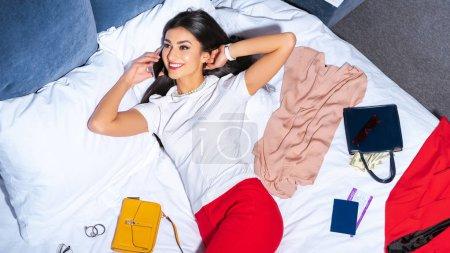 Photo pour Belle femme souriante, parler de smartphone en position couchée sur le lit avec des vêtements élégants, passeport et carte d'embarquement - image libre de droit