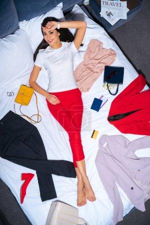 Photo pour Belle jeune femme souriant à la caméra en position couchée sur le lit avec les vêtements à la mode, passeport, carte de crédit et journal de voyage - image libre de droit
