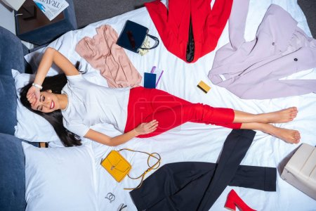 top view of smiling young woman lying on bed with various stylish clothes, handbags and credit card