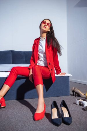 Photo for Attractive young woman in fashionable red suit and sunglasses sitting on bed - Royalty Free Image
