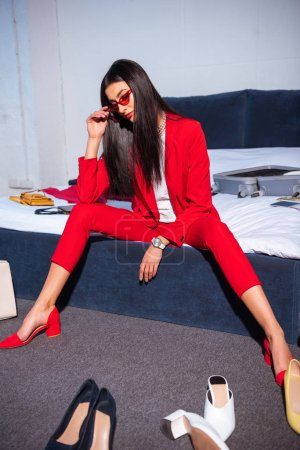 Photo for Beautiful young woman in stylish red suit and sunglasses sitting on bed - Royalty Free Image
