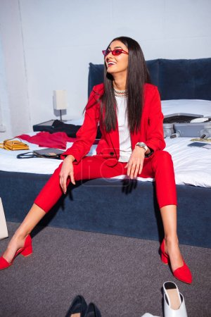 Photo for Beautiful smiling young woman in stylish red suit and sunglasses sitting on bed - Royalty Free Image