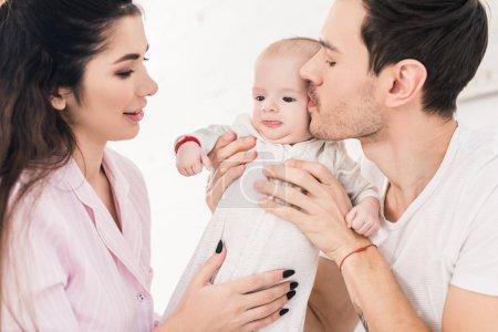 Photo pour Portrait de jeunes parents avec petit fils à la maison - image libre de droit