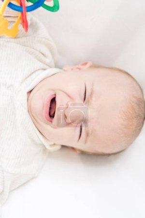 Foto de Vista aérea del pequeño bebé que llora con juguete - Imagen libre de derechos