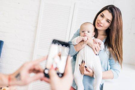 Foto de Toma recortada de hombre tomando foto de esposa con el bebé en las manos en el smartphone - Imagen libre de derechos