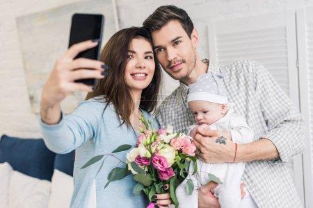 Foto de Retrato de sonriente mujer toma selfie junto con esposo, bebé y ramo de flores en smartphone en el país - Imagen libre de derechos