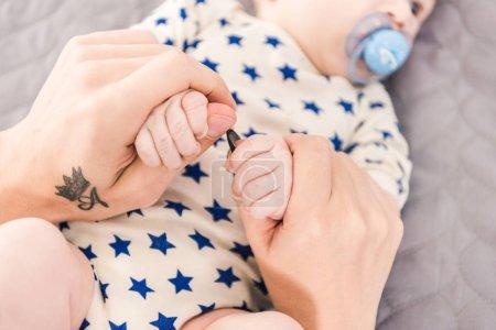 Photo pour Vue partielle du père tenant de petites mains de bébés - image libre de droit