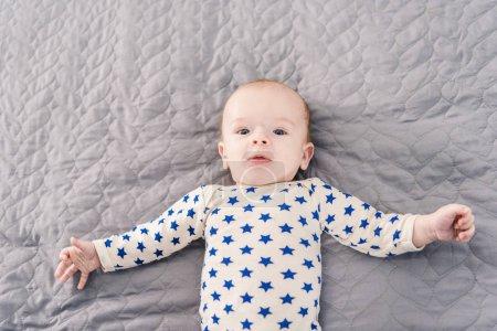 overhead view of adorable little baby lying on grey blanket