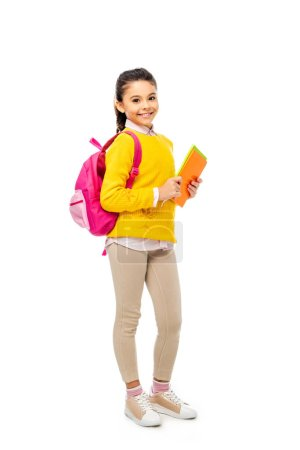 Photo for Adorable kid with backpack holding books while looking at camera isolated on white - Royalty Free Image