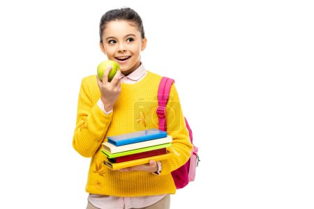 adorable child eating apple and holding books isolated on white