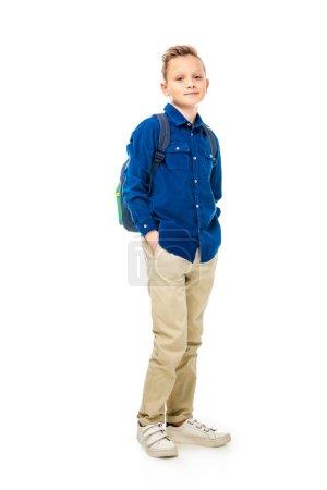 Photo pour Mignon écolier en chemise bleue debout avec les mains dans les poches isolées sur blanc - image libre de droit