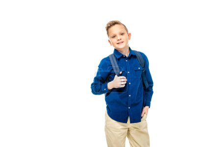 schoolboy in blue shirt with hand in pocket holding backpack straps isolated on white