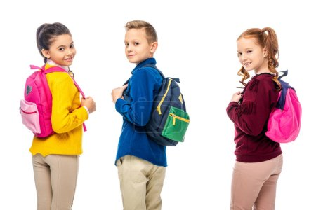 schoolchildren with multicolored backpacks smiling at camera isolated on white