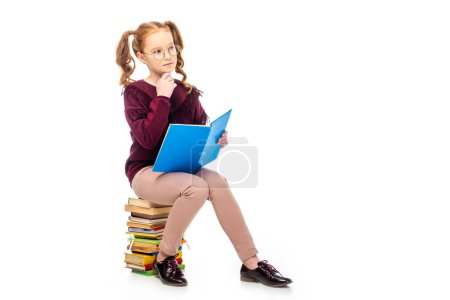 Photo for Thoughtful schoolgirl in glasses sitting on books  isolated on white - Royalty Free Image