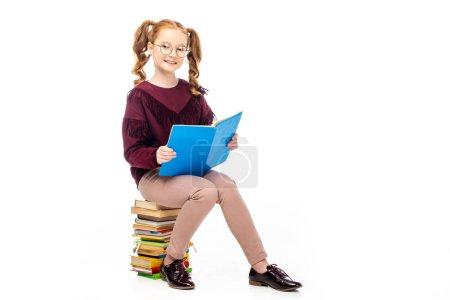 Photo pour Adorable écolière en lunettes assis sur des livres et souriant à la caméra isolé sur blanc - image libre de droit