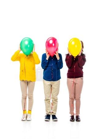 Foto de Niños esconde la cara detrás de coloridos globos aislados en blanco - Imagen libre de derechos