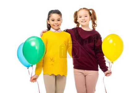 Photo for Smiling schoolgirls embracing, holding multicolored balloons and looking at camera isolated on white - Royalty Free Image