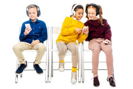 Photo for Cute schoolgirls and boy with headphones looking at smartphone screens isolated on white - Royalty Free Image