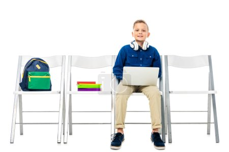 cute boy with headphones on neck sitting on chair, holding laptop and looking at camera isolated on white