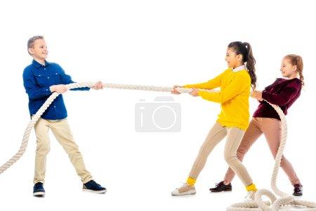 Photo pour Joyeux garçon et deux écolières tirant la corde isolé sur blanc - image libre de droit
