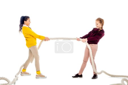 Photo for Two cheerful schoolgirls pulling rope and looking at each other isolated on white - Royalty Free Image