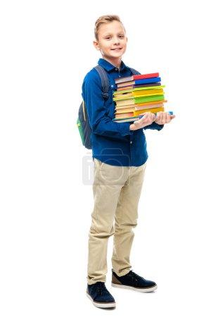Photo pour Garçon mignon avec sac à dos, debout, tenant la pile de livres et regarder la caméra isolé sur blanc - image libre de droit