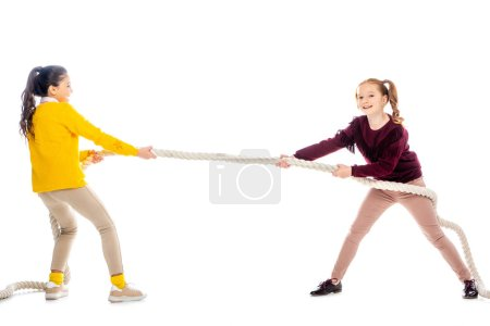 two cheerful schoolgirls pulling rope isolated on white