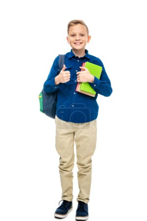 Photo for Smiling schoolboy with backpack holding book and looking at camera isolated on white - Royalty Free Image