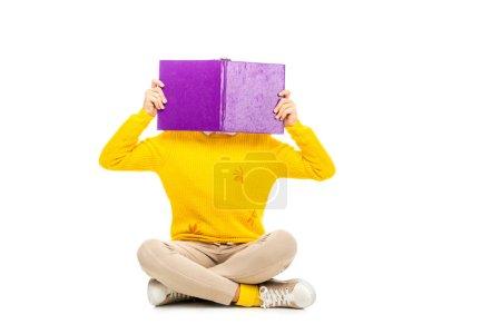 Photo pour Écolière assis et caché visage derrière livre isolé sur blanc - image libre de droit
