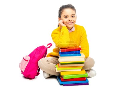 Photo for Cute schoolgirl sitting near stack of books and pink backpack and looking at camera isolated on white - Royalty Free Image