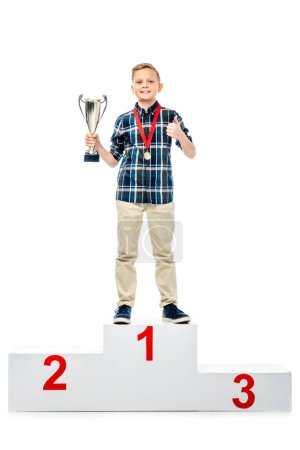 smiling boy standing on winner pedestal, holding trophy cup, showing thumb up and looking at camera isolated on white