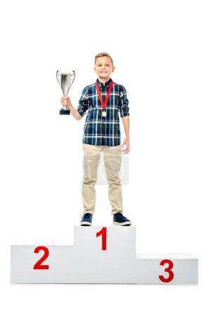 Photo pour Garçon souriant, debout sur socle vainqueur, tenant le trophée coupe et regardant la caméra isolé sur blanc - image libre de droit