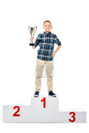 Photo pour Heureux garçon debout sur le podium gagnant, tenant coupe trophée, souriant et regardant la caméra isolée sur blanc - image libre de droit