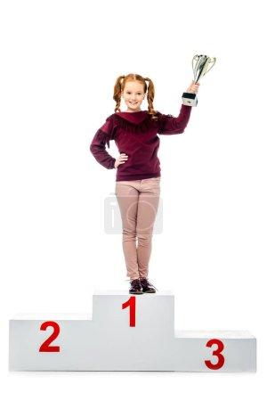 Photo pour Permanent d'écolière gai sur podium gagnant, souriant, tenant le trophée coupe et regardant la caméra isolé sur blanc - image libre de droit