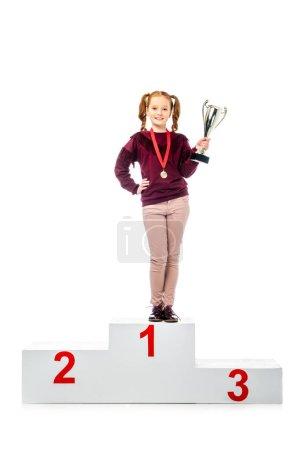 Photo pour Écolière souriante avec médaille debout sur le podium gagnant, tenant coupe trophée et regardant la caméra isolée sur blanc - image libre de droit