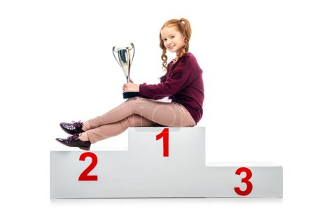 happy schoolgirl sitting on winner podium, holding trophy cup and looking at camera isolated on white