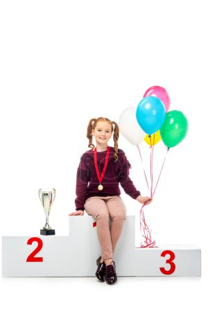 smiling schoolgirl sitting on winner podium near trophy cup, holding colorful balloons and looking at camera isolated on white