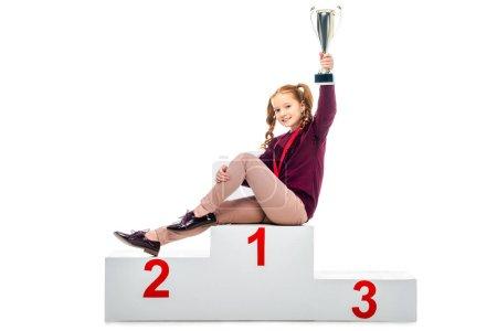 Photo pour Souriant écolière assis sur le podium gagnant, tenant le trophée coupe à main levée et regardant la caméra isolé sur blanc - image libre de droit