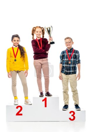 smiling preteen kids with medals and trophy cup standing on winner pedestal, smiling and looking at camera isolated on white