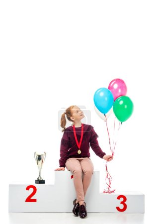 smiling schoolgirl sitting on winner podium near trophy cup and holding colorful balloons isolated on white