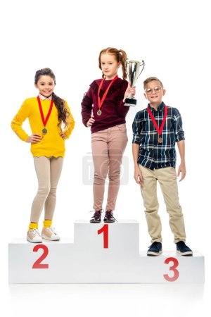 happy kids with medals and trophy cup standing on winner pedestal, smiling and looking at camera isolated on white