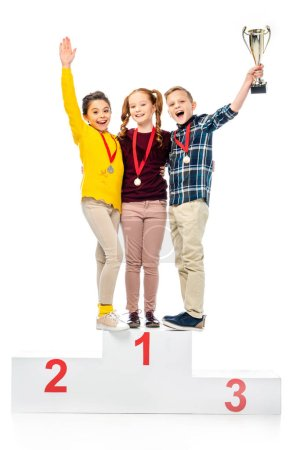 happy kids with medals and trophy cup standing on winner pedestal, shouting and looking at camera isolated on white