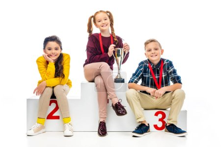 happy kids with medals and trophy cup smiling, sitting on winner pedestal and looking at camera isolated on white