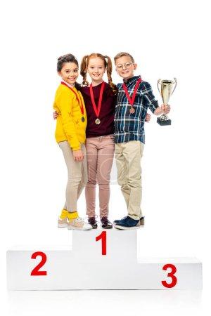 Photo pour Enfants heureux avec médailles et trophée coupe souriant et debout sur le podium gagnant et regardant la caméra isolé sur blanc - image libre de droit