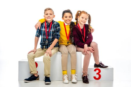 smiling kids with medals sitting on winner podium and looking at camera isolated on white